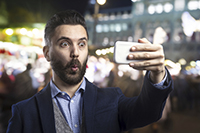Man takes a selfie with his smartphone outside at night in the city