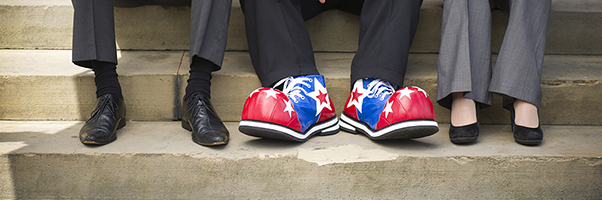 Feet of three lawyers, one wearing clown shoes