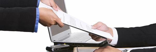 A process server hands a document to a businessman.