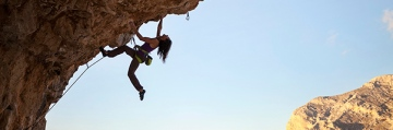 Silhouette of a young female rock climber on a cliff.