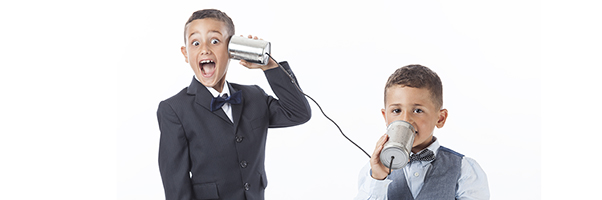 Two boys talking through cans connected by a string.