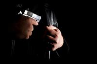 Man drawing a handgun from under his jacket.