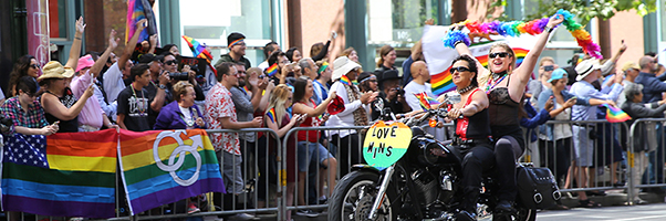 Two women on a motorcycle in a Pride parade