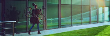 A man, on the way to work, carrying bicycle beside a modern office building.