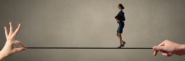 Confident businesswoman walking on rope strained in hands
