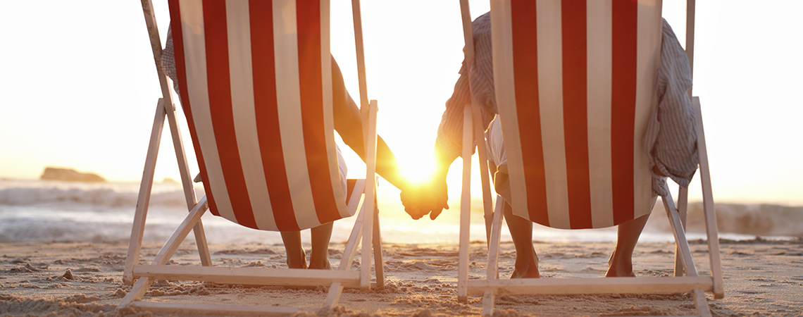 An affectionate couple sitting on the beach alongside copyspace during a pretty sunset
