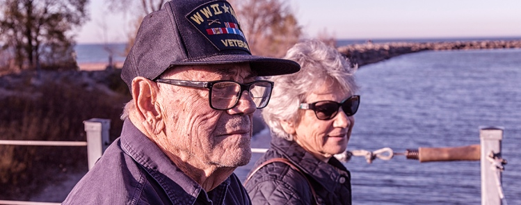 Close-up of a proud, elderly, 93 year old senior adult man USA WWII and Korean Conflict military war veteran and his senior adult woman home caregiver daughter.