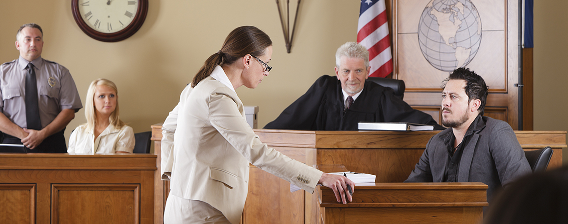 A female lawyer questioning a witness in front of the judge in a courtroom.
